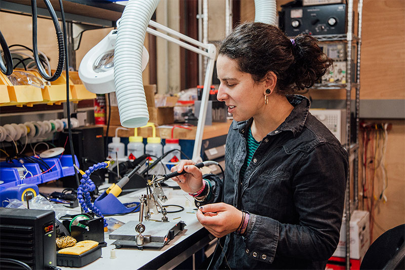 Gabriella uses a soldering iron in an electronics laboratory.