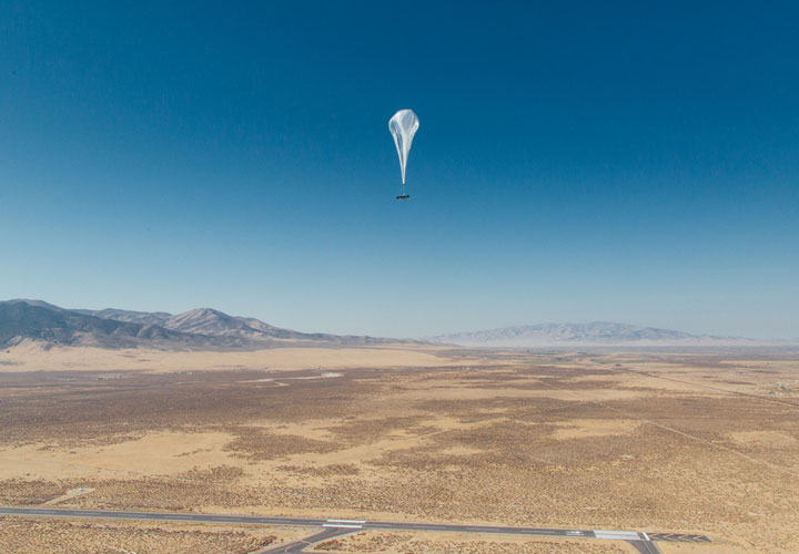 A thin parachute attached to an object flies high over a desert and mountain landscape.