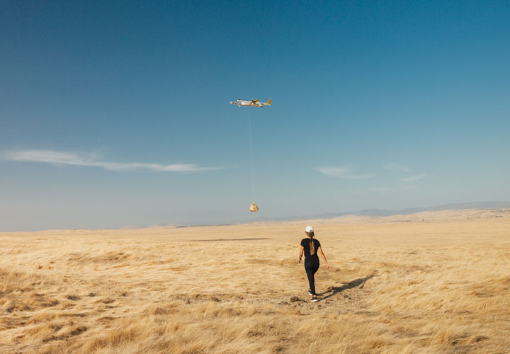 A person wearing a hard hat walks towards a delivery drone n a desert landscape.