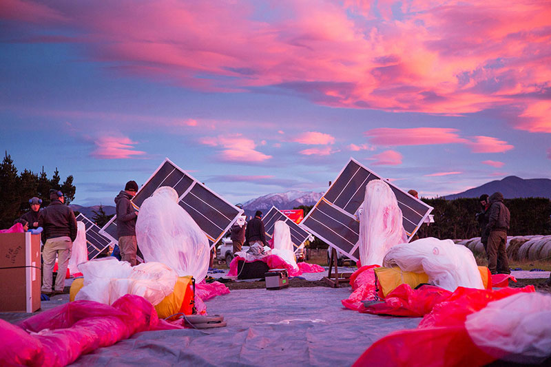 A team busily working with solar panels and colorful, large swaths of fabric under a pink sunset in the desert.